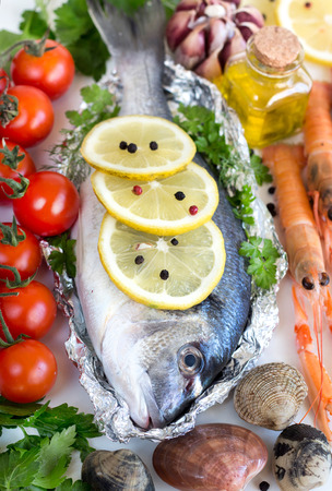 Fresh dorado fish, vegetables, olive oil and seafood photo
