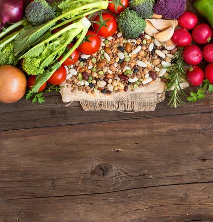 leguminosas: Legumbres mezcladas y verduras en una mesa de madera