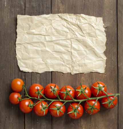 craft paper: Cherry tomatoes and craft paper on wooden background Stock Photo