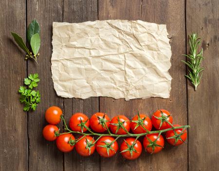 craft paper: Tomates cherry, las hierbas y el papel del arte en el fondo de madera