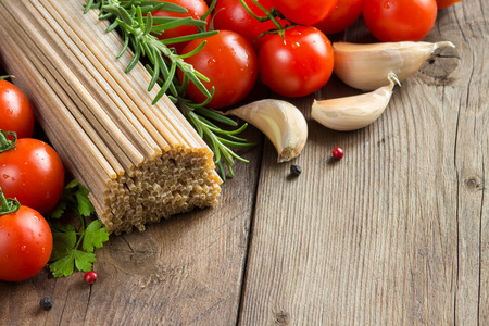 whole wheat: Whole wheat spaghetti, vegetables and herbs on wood