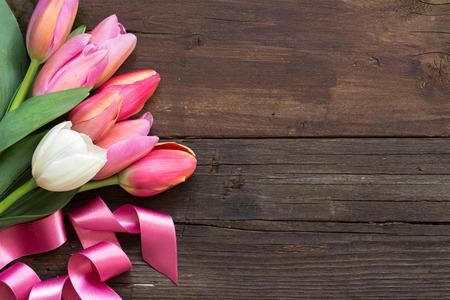 de la madre: Tulipanes rosados ??y blancos en el fondo de madera oscura
