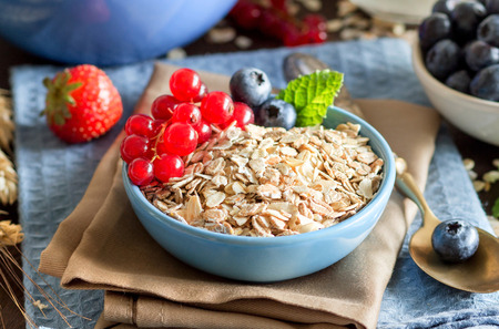 Rolled oats in a blue bowl on a napkin with berries, milk and spoon