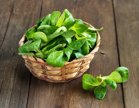 Field salad in a bowl on the old wooden table Archivio Fotografico