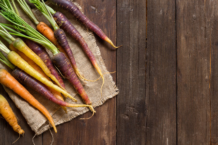 Fresh organic rainbow carrots on a wooden table