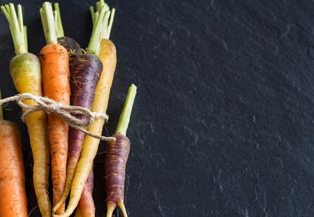 Bunch of fresh organic rainbow carrots on a dark background