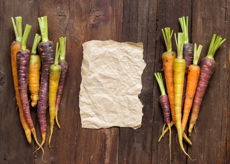 craft paper: Fresh organic rainbow carrots and craft paper on wood