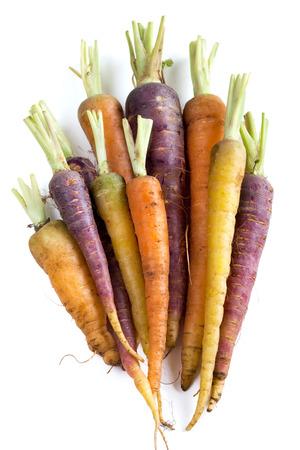 Bos van verse organische regenboog wortelen op wit wordt geïsoleerd