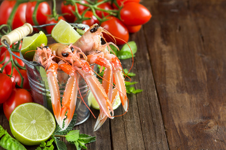 langoustine: Raw langoustine in a bucket with vegetables and herbs on wood