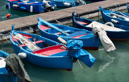 south italy: Blue and red fishing boats in harbour, south Italy Stock Photo