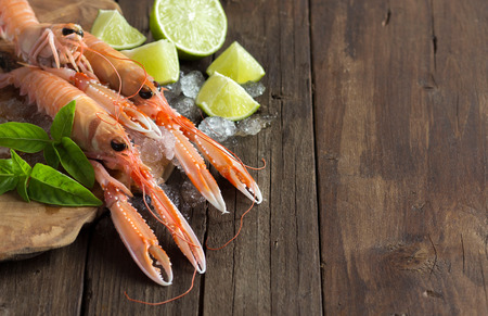 Raw langoustine on ice with lime and basil on wood Archivio Fotografico