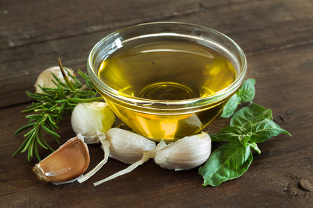 Olive oil, herbs and  garlic on the wooden table