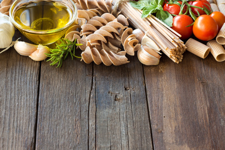 olive green: Olive oil, pasta, garlic and tomatoes on the wooden table