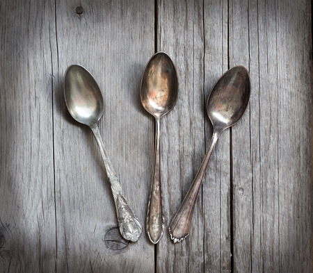 grunge silverware: Vintage spoons with patina on old  wooden table