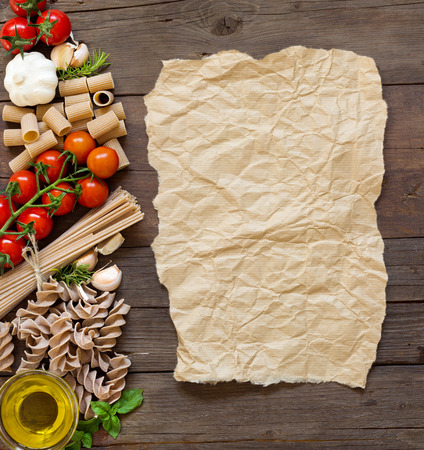 craft paper: Olive oil, pasta, garlic and tomatoes with craft paper on the wooden table