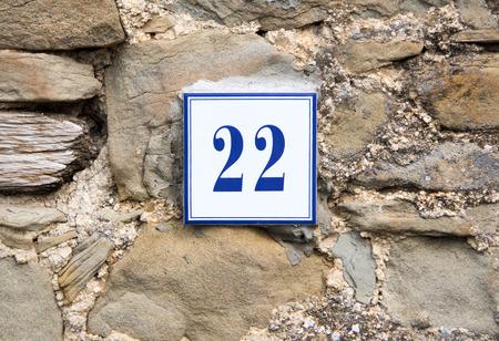 twenty two: Ceramic number twenty two on the grey stone wall