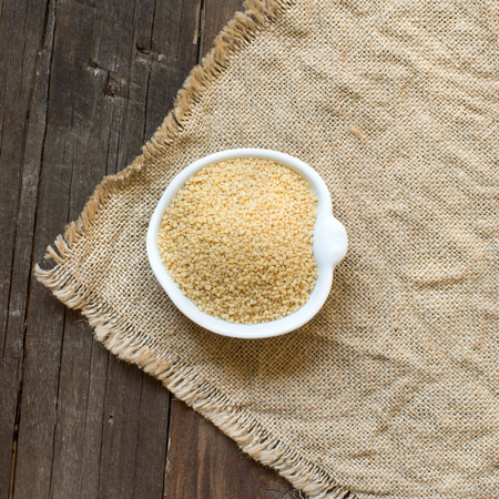 wheat kernel: CousCous in a bowl on burlap and wooden table