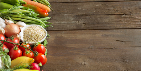 raddish: Quinoa in a bowl and fresh vegetables on a wooden table Stock Photo