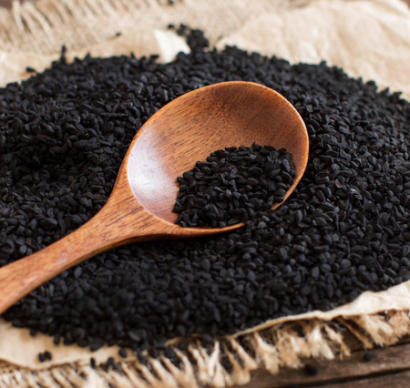 Nigella sativa or Black cumin with a spoon close up