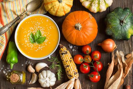 comidas saludables: Sopa de calabaza y hortalizas frescas en una mesa de madera
