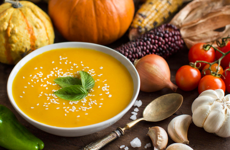 harvest: Fresh pumpkin soup with a spoon and vegetables on a wooden table