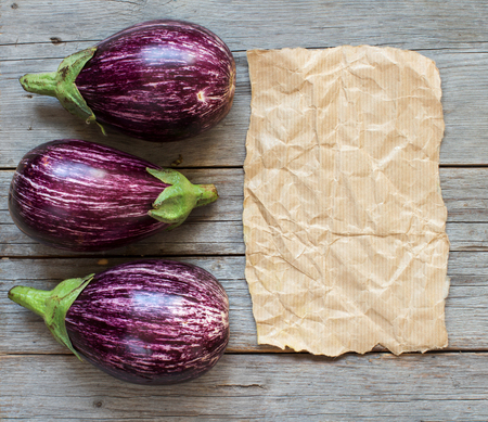 craft paper: Fresh Raw striped eggplants and craft paper on a old wooden table
