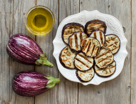 grilled vegetables: Grilled eggplants seasoned with olive oil on a wooden table Stock Photo