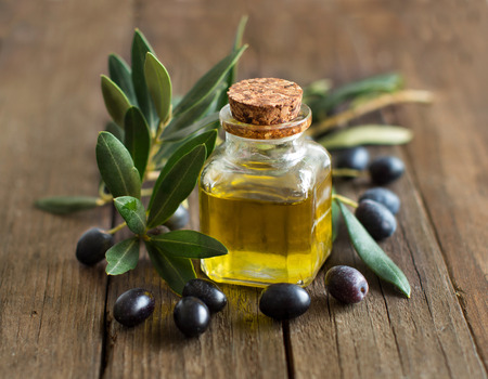 Olive oil and fresh olives on rustic wood background