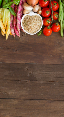 unpolished: Unpolished raw rice and vegetables on a wooden background Stock Photo