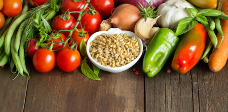 legumbres secas: Deletreada en un bol y las verduras frescas sobre una mesa de madera