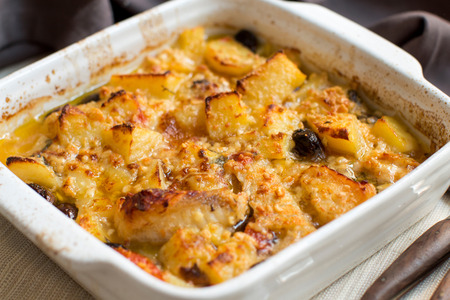 Fish with potatoes  and olives cooked in oven in small casserole
