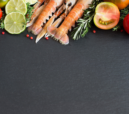 raw lobster: Raw langoustines with vegetables and herbs on the dark background
