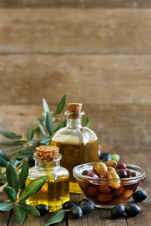 foglie ulivo: Olio d'oliva e olive su sfondo di legno rustico Archivio Fotografico