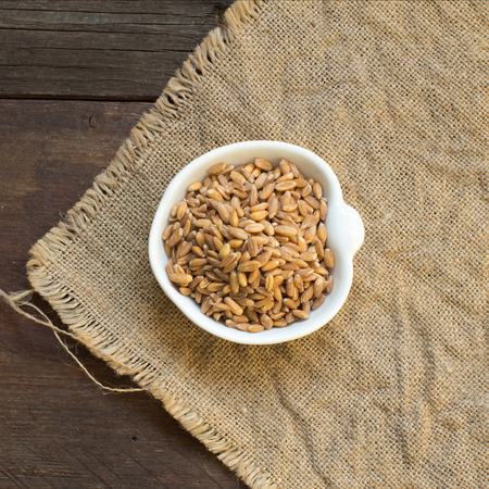 unpolished: Whole unpolished spelt in a bowl on wood