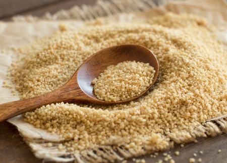 wheat kernel: Pile of whole wheat CousCous with a spoon close up