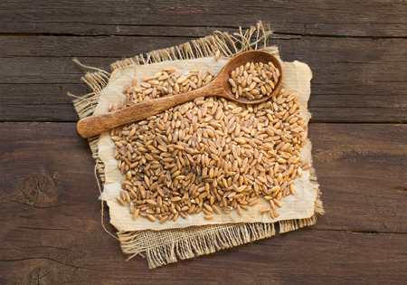 unpolished: Whole unpolished spelt in a with a spoon on wooden table Stock Photo