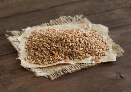 unpolished: Pile of whole unpolished spelt  on wooden table