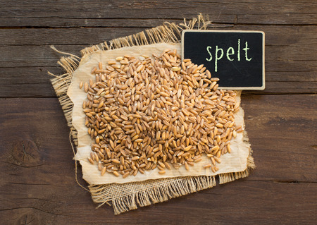 unpolished: Whole unpolished spelt in a with a small chalkboard on wooden table Stock Photo