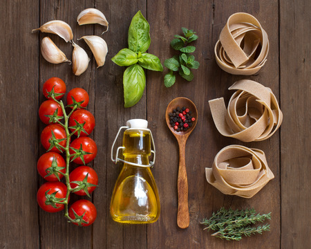 cooking oil: Whole wheat  pasta, vegetables,  herbs and olive oil on wooden background Stock Photo