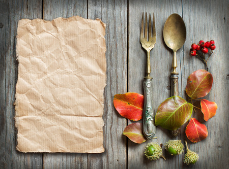 recipe background: Vintage fork and knife with fall leaves, acorns and berries on the old wooden table Stock Photo
