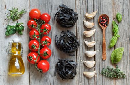 tomate: Sec p�tes tagliatelles noir avec des tomates cerises, de l'ail et des herbes sur le bois