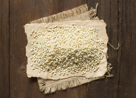 morsel: White Sorghum grain on wooden table  close up Stock Photo