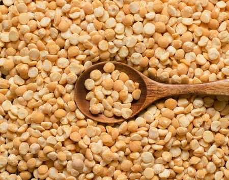 split up: Uncooked Yellow split peas with a spoon close up
