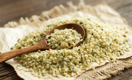 Pile of Uncooked Hemp seeds with a spoon close up Stock Photo