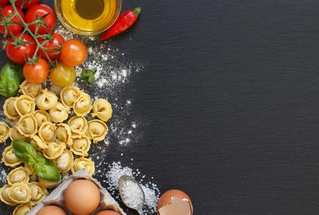 Pasta fresca y los ingredientes en una tabla oscura Foto de archivo - 53106233