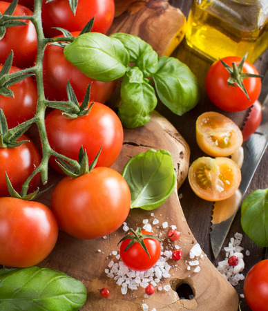 olive green: Cherry tomatoes, basil and olive oil on a wooden table Stock Photo