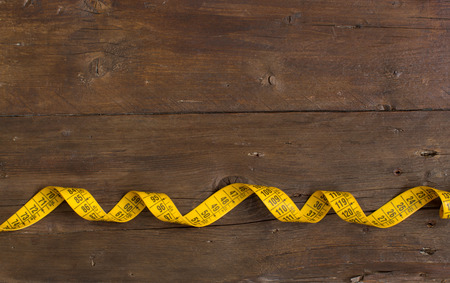 Yellow measuring tape on old wood top view