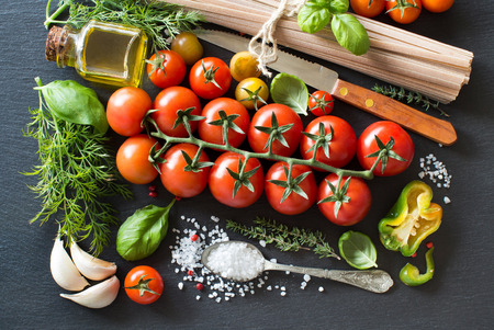 ingridients: Italian cooking ingridients : cherry tomatoes, herbs, pasta and olive oil on a dark background
