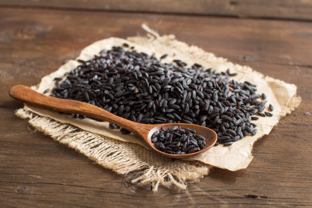 Pile of black rice with a spoon on a wooden table Stock Photo