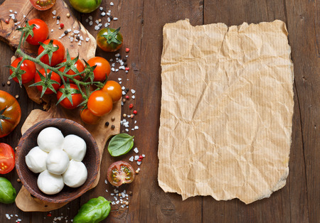 brown paper: Italian cooking ingredients : mozzarella, tomatoes, basil, olive oil and other Stock Photo